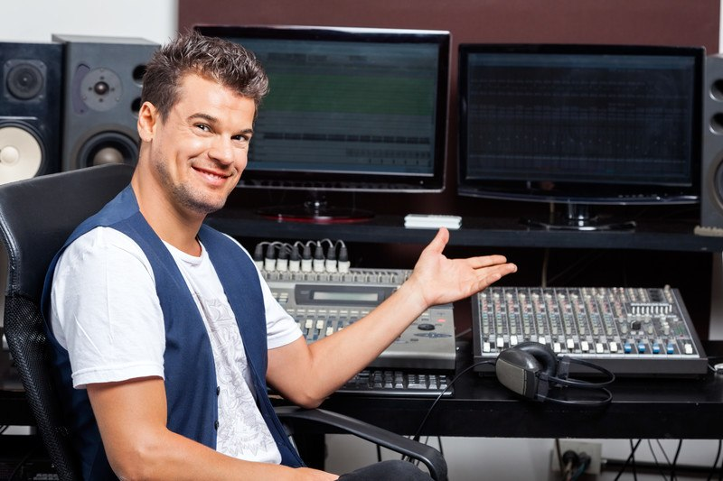 This photo shows a smiling man in a white tee shirt and blue vest holding a hand in front of high-tech audio equipment, representing the question, do audio engineers make good money?