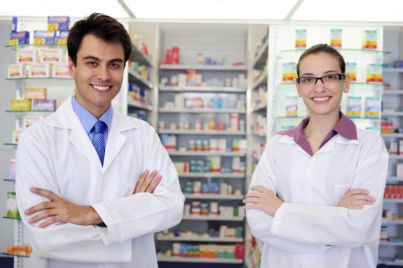 This photo shows a smiling man and a smiling woman in white lab coats, folding their arms and standing in front of shelves of medicines in a pharmacy, representing the question, do pharmacy techs make good money?