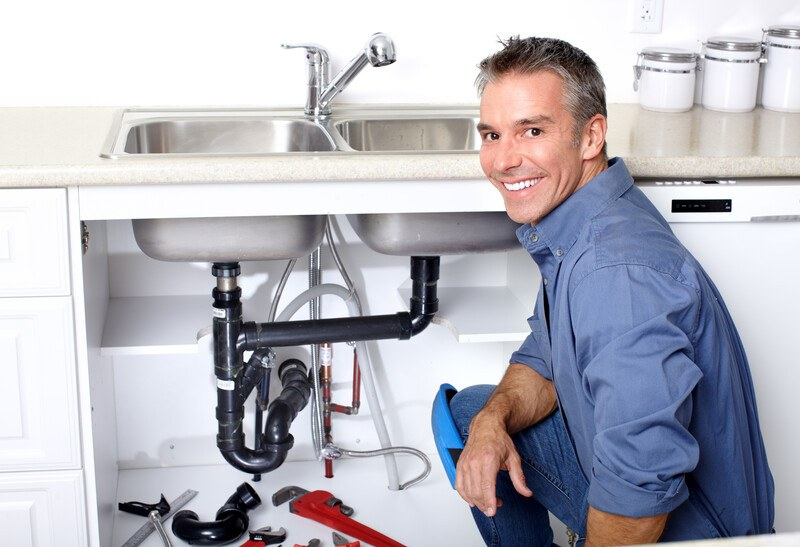 This photo shows a smiling man in a blue shirt and jeans kneeling next to an open sink and tools, representing the question, do plumbers make good money?