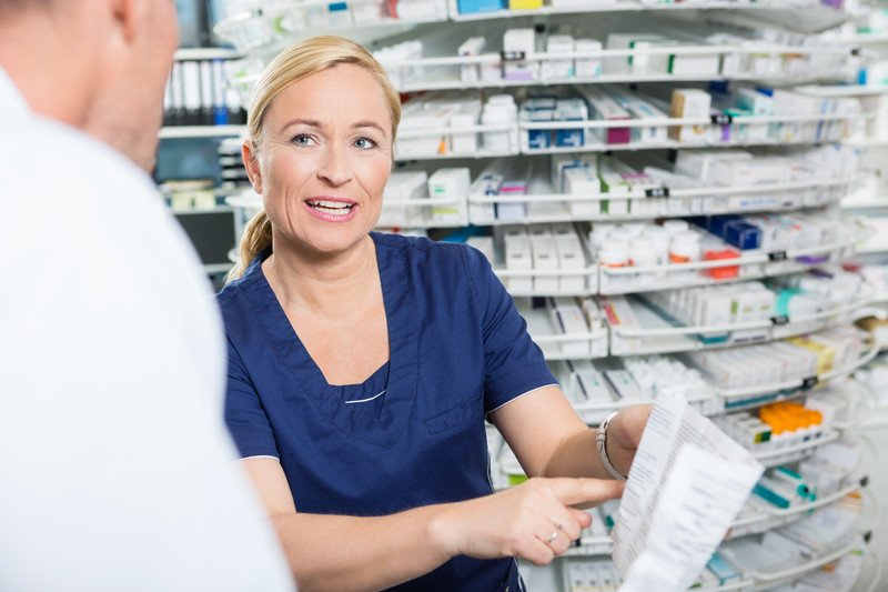 This photo shows a smiling blonde woman pharmacy tech talking to a pharmacist in a white coat about a prescription.