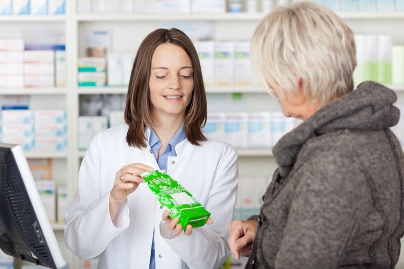 This photo shows a brunette woman pharmacy tech showing prescription in a green bag to a woman with short blonde hair and a brown coat.