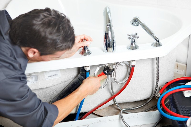 This photo shows the back view of a dark-haired plumber in charcoal-colored clothing using a wrench to tighten a pipe fitting on a bathtub that includes red and blue hoses under the lip of the tub.
