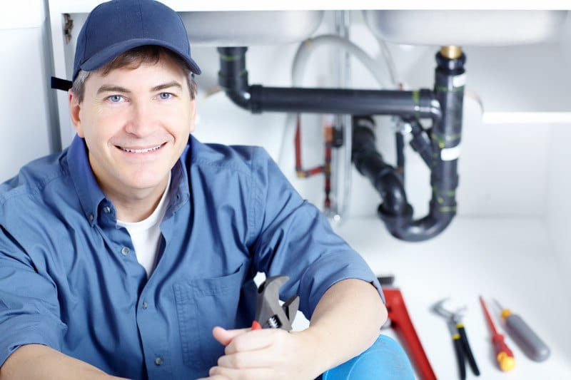 This photo shows a smiling man in a blue hat and blue clothes, holding a wrench and sitting in front of a set of tools and pipes under a sink.