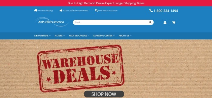 This screenshot of the home page for Air Purifiers America has a red header, a blue header, and a blue navigation bar with white text above a closeup photo of a piece of corrugated cardboard with a red stamped announcement for warehouse deals on it, along with a black call to action button.