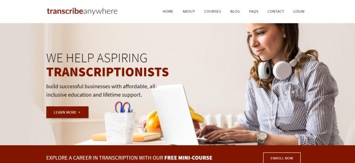 This screenshot of the home page for Transcribe Anywhere has a white header with black and maroon text above a large photo showing a woman with a headset, typing on a laptop on a table near fruit and a basket containing pens and scissors, behind black and maroon text with a maroon call to action button.