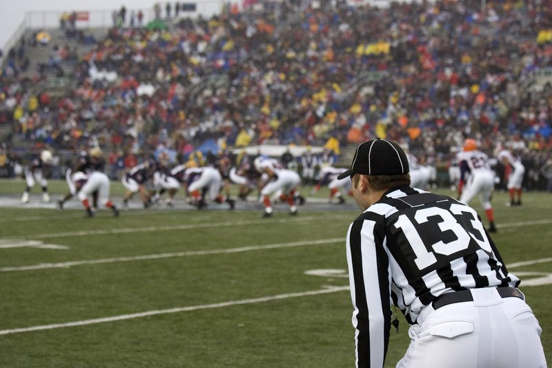 This photo shows a packed stadium, football players on the field, and a referee, representing the best college sports affiliate programs.