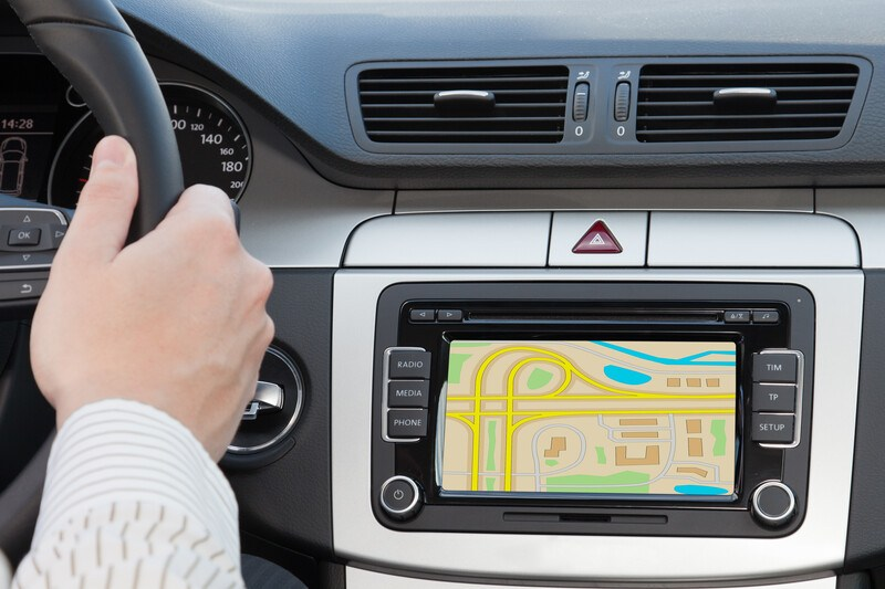 This photo shows a multicolored screen on a GPS unit installed in a luxury vehicle, while a man's hand rests on the steering wheel, representing the best GPS affiliate programs.