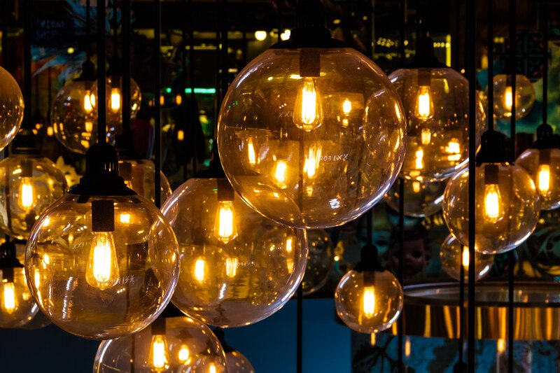This photo shows a set of interesting light fixtures with small lights inside of glass globes against a dark background, representing the best lighting affiliate programs.