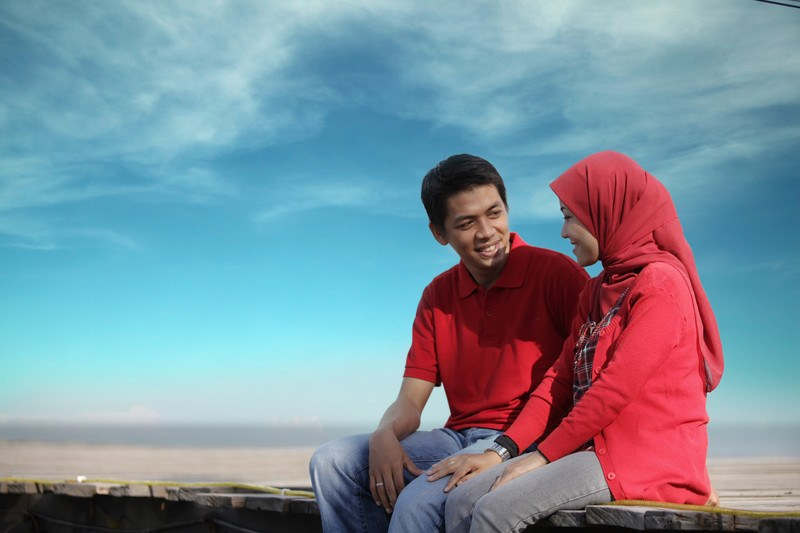 This photo shows a smiling couple in red shirts and jeans, with the woman wearing a red hijab, sitting on a boardwalk beneath a blue sky, representing the best religious dating affiliate programs.