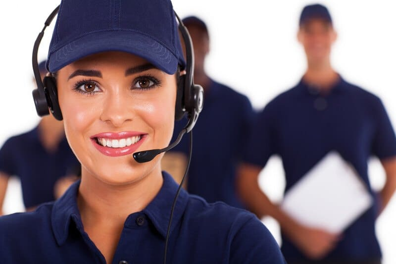 This photo shows a smiling dark-eyed woman in blue clothes, a blue hat, and a headset standing in front of a team of men in blue clothing.