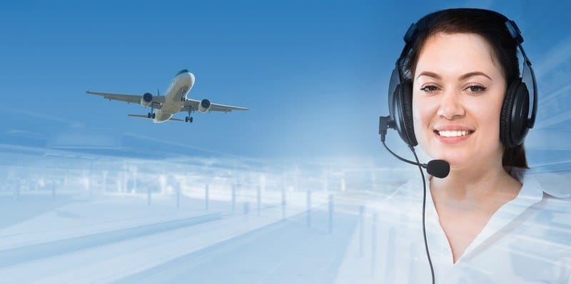 This photo shows a blue sky with an airplane flying on the left and a smiling dark-haired woman in a headset on the right, representing the question, do dispatchers make good money?