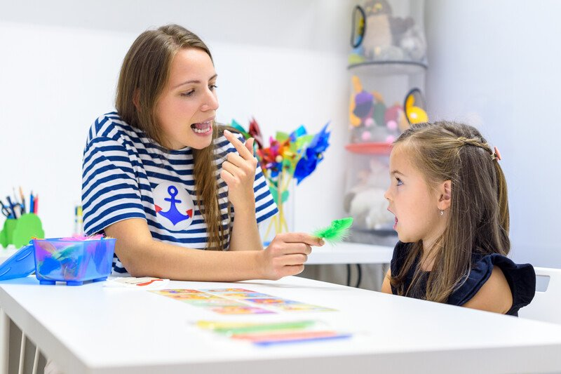 This photo shows a speech pathologist with long brown hair in a blue and white striped shirt showing a tongue position to a brunette girl in a white-walled classroom with multicolored toys and a white table.