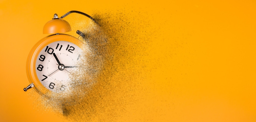 Dissolving orange clock to represent the risk of losing time