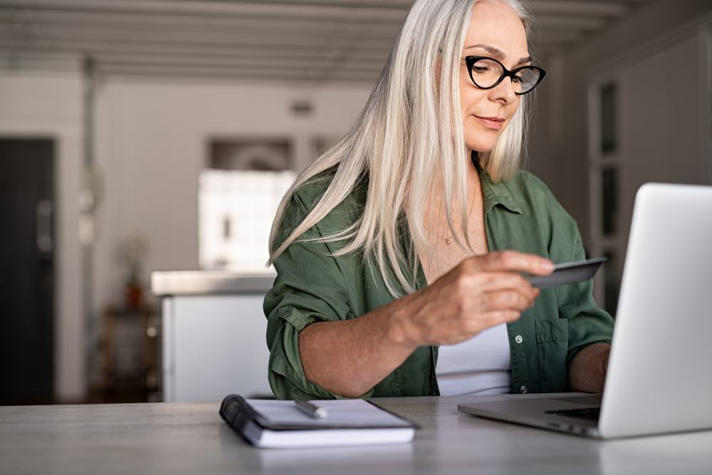 older woman using credit card to shop online