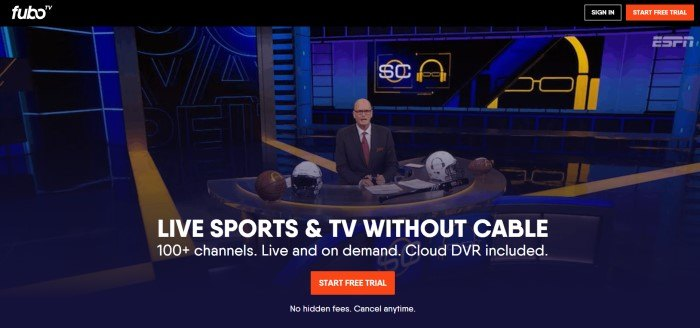 This screenshot of the home page for FuboTV has a large photo of a production studio with blue, black, and yellow elements, as well as a man wearing a suit and glasses behind a desk with four football helmets on it, behind white text and a red call to action button.