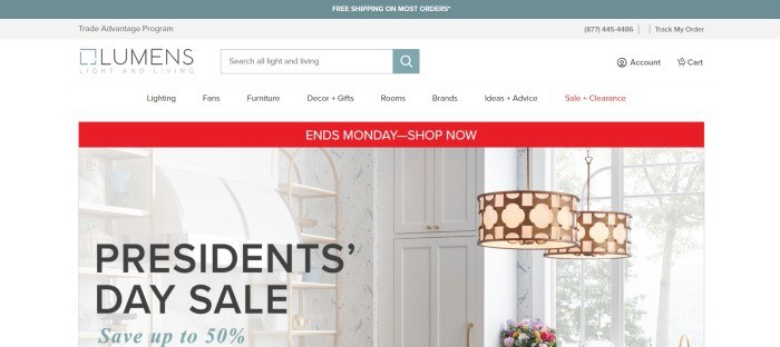 This screenshot of the home page for Lumens has a gray header, a white search bar and navigation bar, a red announcement bar, and a photo of some interesting light fixtures hanging in a white kitchen.