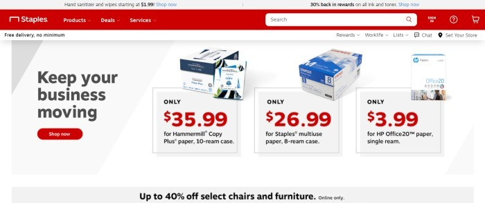 This screenshot of the home page for Staples has a gray header, a red navigation bar and search bar, a white announcement bar, and a gray main section with black text, product photos showing boxes of paper, and a red call to action button.