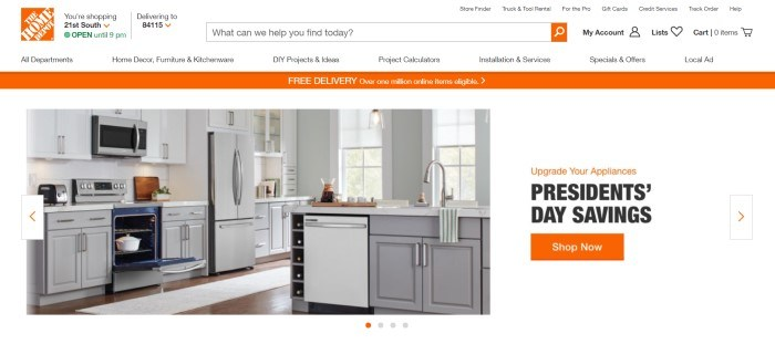 This screenshot of the home page for The Home Depot has an orange and white logo in the upper left, a white search bar and navigation bar, an orange announcement bar, and a photo of a white kitchen with stainless steel appliances next to an orange and white announcement section with an orange call to action button.