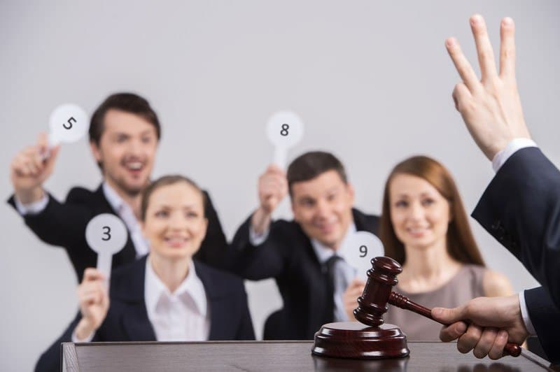 This photo shows four smiling men and women in business clothing holding paddles behind a table where an auctioneer's hand is showing three fingers, and his other hand is clapping a wooden mallet on its pedestal, representing the best auction affiliate programs.