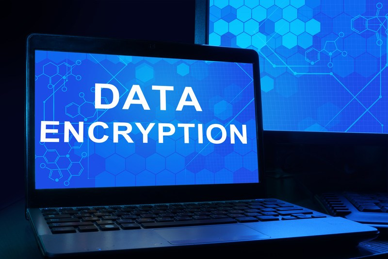 This photo shows a large blue lit computer monitor behind an open laptop with a similarly lit blue screen with white text reading 'data encryption,' representing the best encryption affiliate programs.