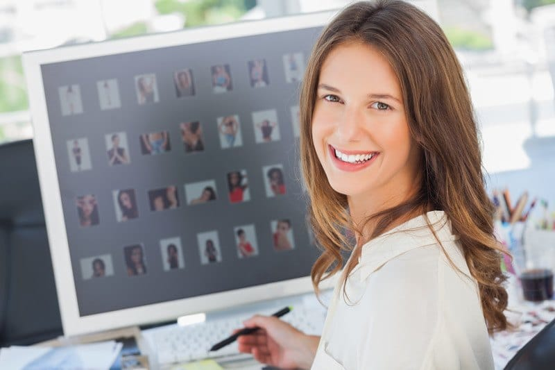 This photo shows a smiling brunette woman in a white shirt editing photos on a computer screen, representing the best Photoshop affiliate programs.