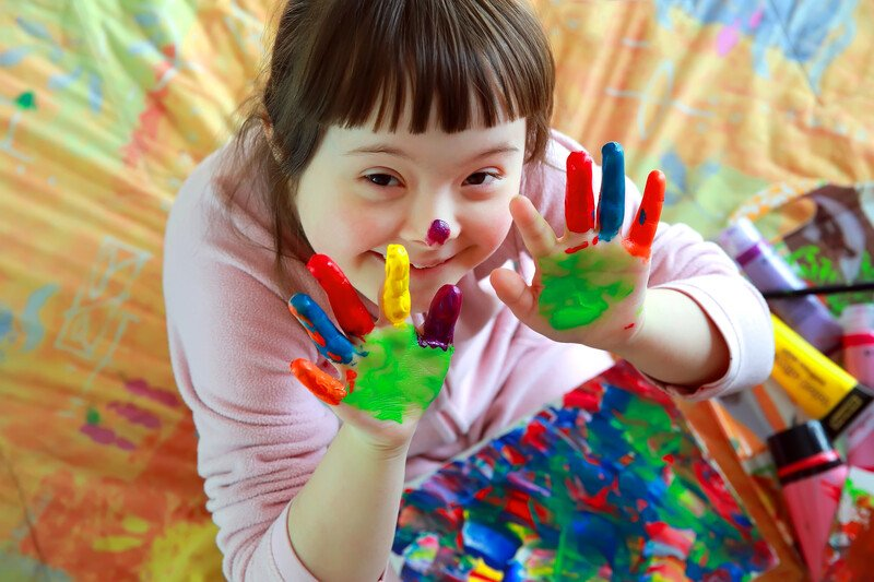 This photo shows a smiling brunette Downs Syndrome girl with colorful paint on her fingers, representing the best special needs affiliate programs.