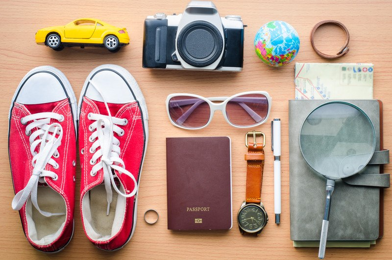 This photo features a passport, ring, watch, sunglasses, camera red sneakers, small yellow camera, a ball with a world map on it, and other travel-related items, representing the best travel accessories affiliate programs.