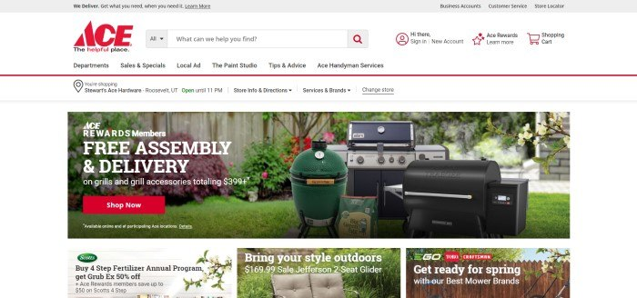 This screenshot of the home page for Ace Hardware has a gray header, a white navigation and search bar with black and red text, a white announcement bar, and a photo showing several types of barbecue grills in a green back yard, along with white text and a red call to action button.