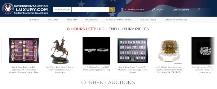 This screenshot of the home page for Auction King has a blue header with a flag fading into it and a search bar across the top, a white navigation bar, and a white main section with red and black text and a row of photos of high-end items, including figurines, stamps, and rings, to be auctioned.