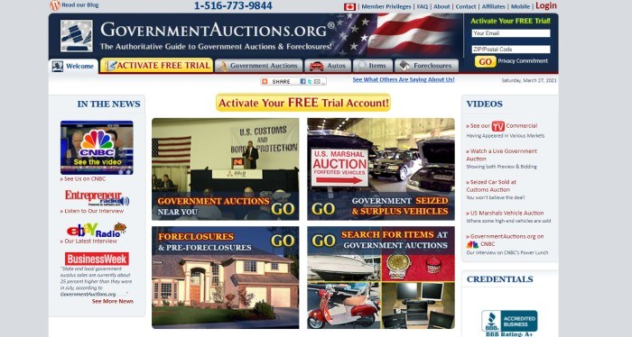 This screenshot of the home page for GovernmentAuctions.org has a gray surrounding section, a blue header with a flag photo faded into it, a gray and gold navigation bar, and a white main section containing media inclusions on the left side of the page, video links on the right side of the page, and four pictures in the center of the page depicting auction scenes for a variety of goods, as well as a gold call to action button.
