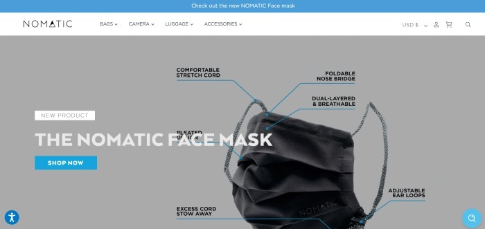 This screenshot of the home page for Nomatic has a blue header, a white navigation bar, and a gray main section featuring a black face mask with labels, white and black text, and a blue call to action button.