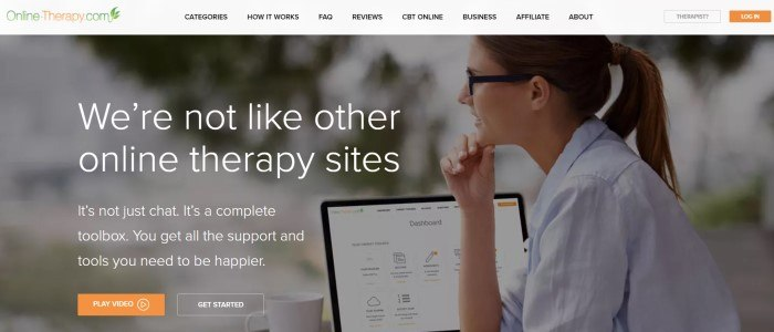 This screenshot of the home page for Online Therapy has a gray header with an orange and green logo above a photo of a smiling woman in glasses sitting in front of an open laptop, behind white text and an orange call to action button.