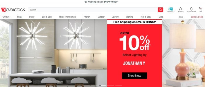This screenshot of the home page for Overstock.com has a white header, navigation bar, and search bar above a photo on the left side of the page showing a kitchen with star-shaped chandeliers hanging above a white counter and white stools, and a photo of a lamp with a beige lampshade on the right side of the page, behind a red and white sales announcement.