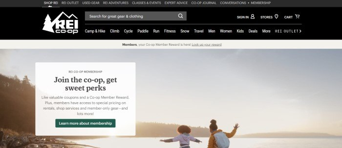 This screenshot of the home page for REI has a black header, search bar, and navigation bar with white text above a beige announcement bar and a large photo showing two dark-haired girls playing at the edge of a lake near sunset, with a white text box on the left side of the page containing black text and a green call to action button.