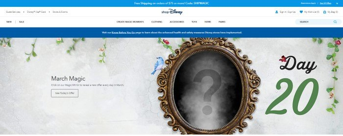 This screenshot of the home page for ShopDisney has a blue header, a white navigation bar, a blue announcement bar, and a gray main section featuring a magic mirror with an ornate gold frame and a question mark in the center, along with tendrils of plants and birds around the edge of the picture, black text on the left side of the page, and a transparent call to action button.