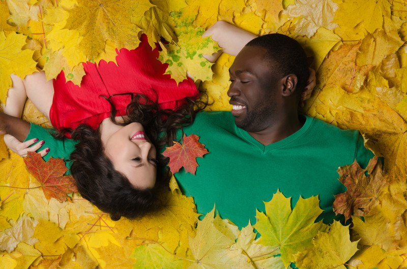 This photo shows a smiling dark skinned man in a green shirt and a smiling Asian woman in a red shirt playing together in a pile of yellow maple leaves, representing the best race dating affiliate programs.