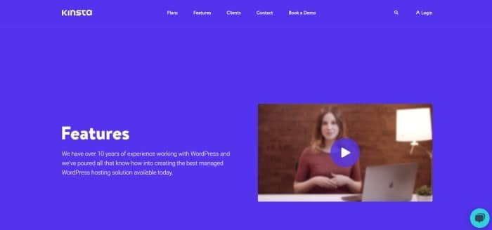 This screenshot of the home page for Kinsta has a royal blue background and header with white text, as well as a video clip on the right side of the page showing a still shot of a woman in a red shirt sitting at a table near an open laptop.